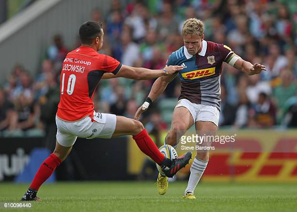 Matt Hopper of Harlequins has his kick charged down by Alex Lozowski of Saracens during the Aviva Premiership match between Harlequins and Saracens...