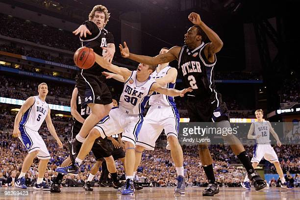 Matt Howard and Shawn Vanzant of the Butler Bulldogs battle for the ball with Jon Scheyer and Miles Plumlee of the Duke Blue Devils during the 2010...