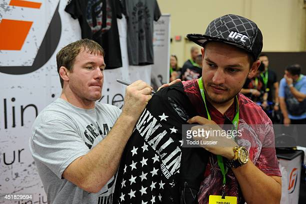 Matt Hughes signs an autograph for fans during the UFC Fan Expo 2014 during UFC International Fight Week at the Mandalay Bay Convention Center on...