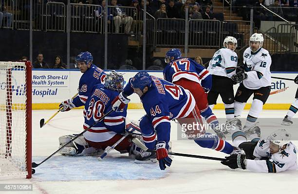 Matt Hunwick of the New York Rangers reaches to stop the puck from crossing the goal line as Logan Couture of the San Jose Sharks hits the ice during...