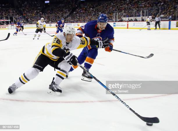 Matt Hunwick of the Pittsburgh Penguins carries the puck around Anders Lee of the New York Islanders during the second period at the Barclays Center...
