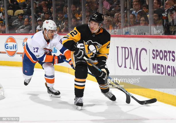 Matt Hunwick of the Pittsburgh Penguins handles the puck against Anders Lee of the New York Islanders at PPG Paints Arena on December 7 2017 in...