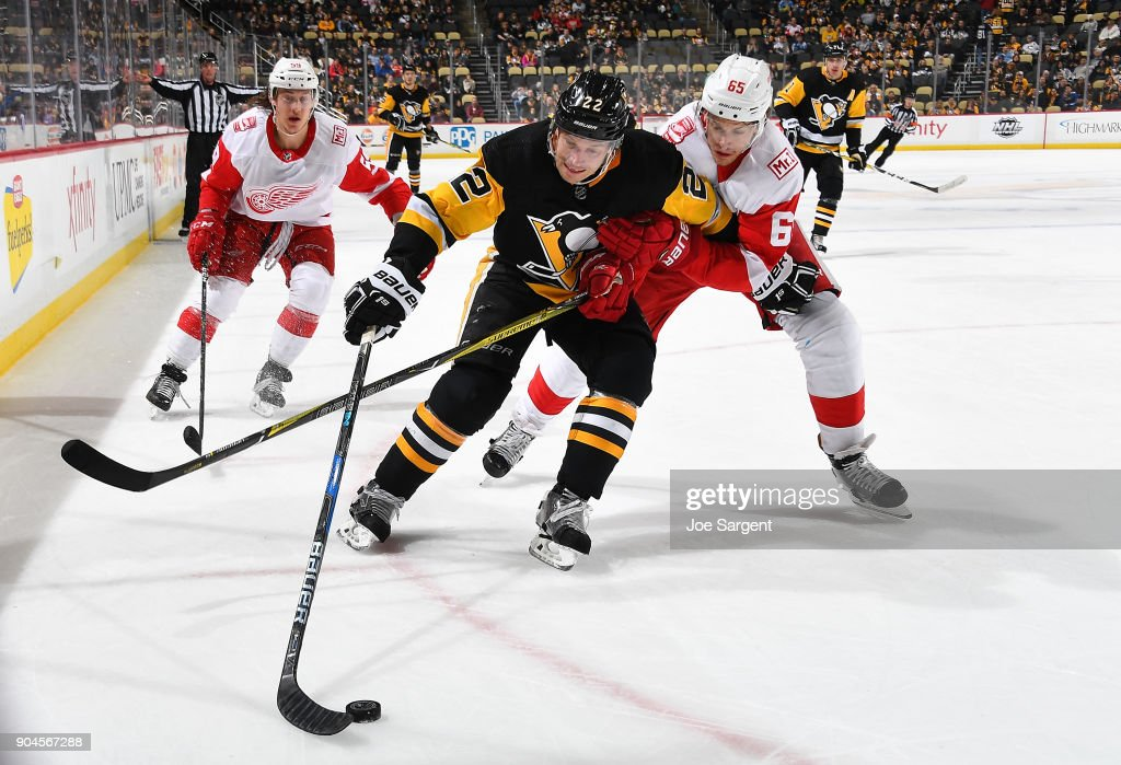 Matt Hunwick #22 of the Pittsburgh Penguins handless the puck against Danny DeKeyser #65 of the Detroit Red Wings at PPG Paints Arena on January 13, 2018 in Pittsburgh, Pennsylvania.
