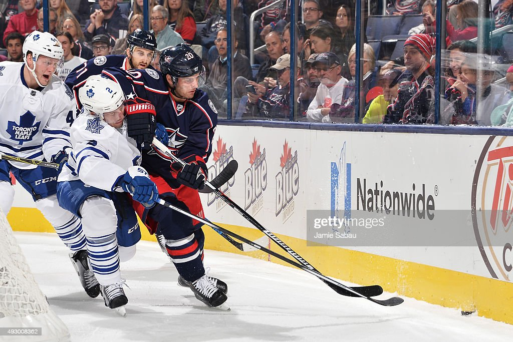 Matt Hunwick #2 of the Toronto Maple Leafs and Brandon Saad #20 of the Columbus Blue Jackets battle for the puck behind the net during the first period on October 16, 2015 at Nationwide Arena in Columbus, Ohio.