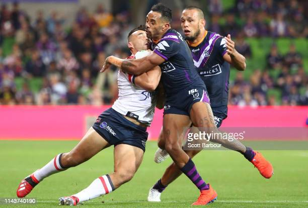 Matt Ikuvalu of the Roosters is tackled by Josh AddoCarr of the Melbourne Storm during the round 6 NRL match between the Melbourne Storm and the...