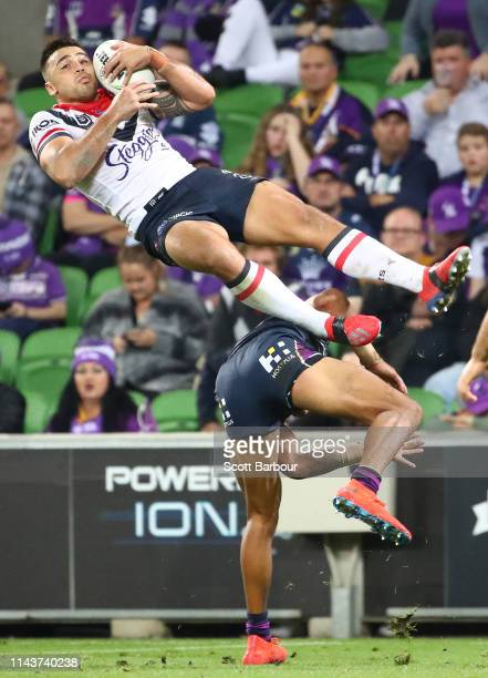 Matt Ikuvalu of the Roosters is upended by Josh AddoCarr of the Melbourne Storm during the round 6 NRL match between the Melbourne Storm and the...