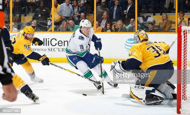 Matt Irwin of the Nashville Predators lifts the stick of Jake Virtanen of the Vancouver Canucks as he skates in on Pekka Rinne during an NHL game at...