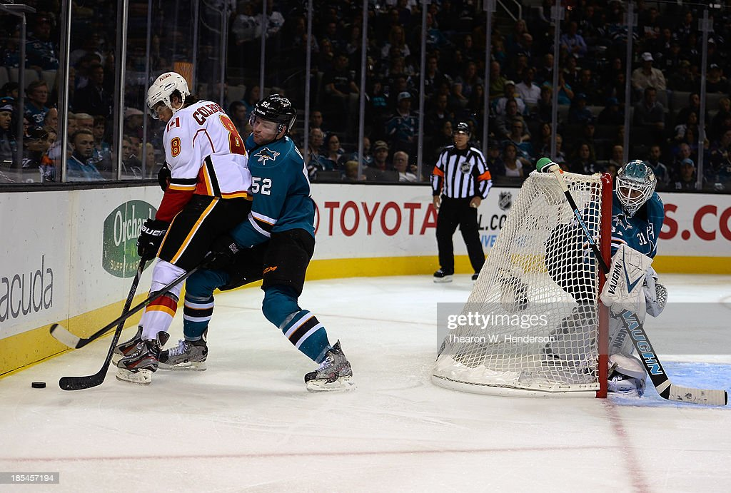 Matt Irwin #52 of the San Jose Sharks battle for control of the puck with Joe Colborne #8 of the Calgary Flames at SAP Center on October 19, 2013 in San Jose, California.