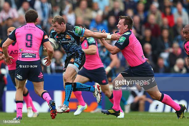 Matt Jess of Exeter Chiefs powers past Matthew Rees of Cardiff Blues on his way to scoring a try during the Heineken Cup Pool Two match between...