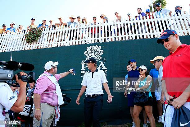 Matt Jones of Australia and his caddie Shannon Wallis check their options after Jones drive into a hospitality tent on the ninth hole during the...