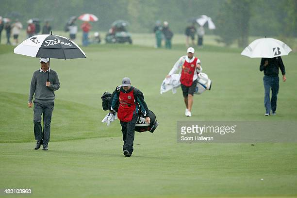 Matt Jones of Australia and Matt Kuchar of the United States walk with their caddies after on the fairway in the first hole of the playoff in the...
