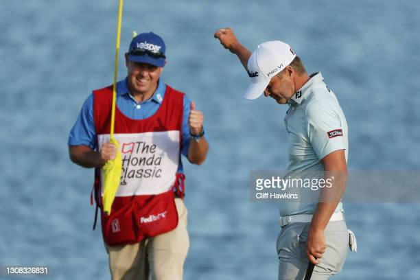 Matt Jones of Australia celebrates with caddie Lance Bailey after winning on the 18th green during the final round of The Honda Classic at PGA...