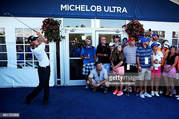 Matt Jones of Australia plays his second shot from the carpet of a hospitality tent during the third round of the 2015 PGA Championship at Whistling...