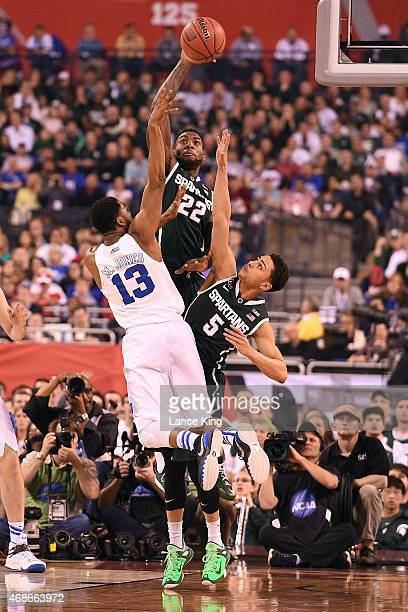 Matt Jones of the Duke Blue Devils puts up a shot against Branden Dawson and Bryn Forbes of the Michigan State Spartans during the NCAA Men's Final...