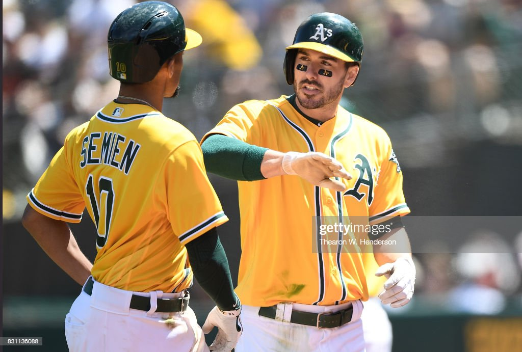 Matt Joyce #23 and Marcus Semien #10 of the Oakland Athletics celebrates after Joyces scored on a sacrifice fly ball from Semien against the Baltimore Orioles in the bottom of the fifth inning at Oakland Alameda Coliseum on August 13, 2017 in Oakland, California.