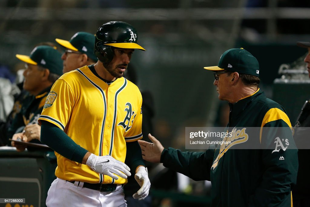 Matt Joyce #23 of the Oakland Athletics celebrates with Manager Bob Melvin #6 after scoring on a double hit by Khris Davis #2 of the Oakland Athletics in the fifth inning against the Chicago White Sox at Oakland Alameda Coliseum on April 16, 2018 in Oakland, California.