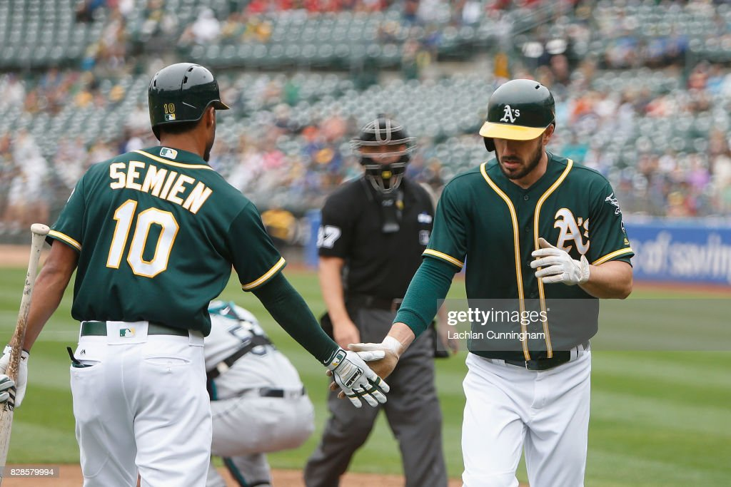 Matt Joyce #23 of the Oakland Athletics celebrates with Marcus Semien #10 after hitting a solo home run in the first inning against the Seattle Mariners at Oakland Alameda Coliseum on August 9, 2017 in Oakland, California.