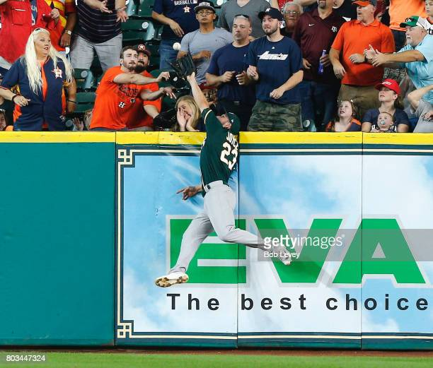 Matt Joyce of the Oakland Athletics makes a leaping catch at the wall on fly ball by Josh Reddick of the Houston Astros in the first inning at Minute...