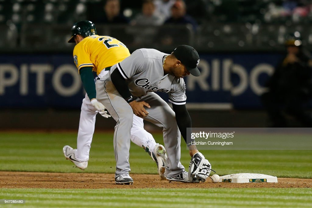 Matt Joyce #23 of the Oakland Athletics reaches first base as Yoan Moncada #10 of the Chicago White Sox is unable to pick up the ball after an error by Jose Abreu #79 of the Chicago White Sox in the seventh inning at Oakland Alameda Coliseum on April 16, 2018 in Oakland, California.