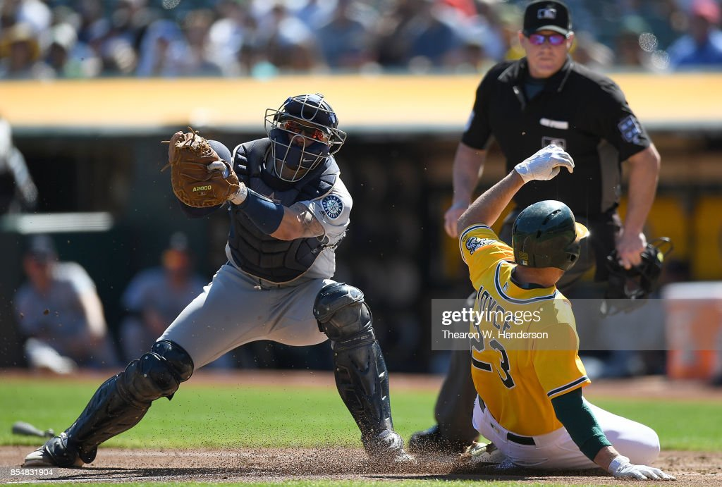 Matt Joyce #23 of the Oakland Athletics scores sliding past catcher Mike Marjama #28 of the Seattle Mariners in the bottom of the first inning at Oakland Alameda Coliseum on September 27, 2017 in Oakland, California.