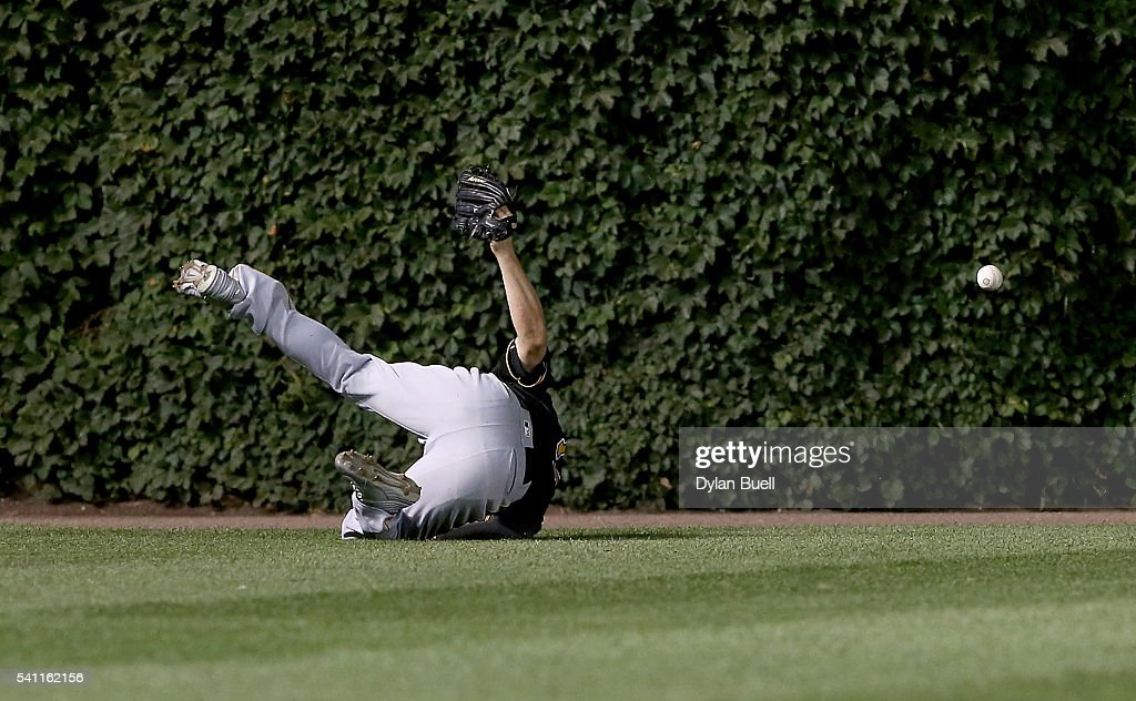 Matt Joyce #17 of the Pittsburgh Pirates dives in an attempt to catch a fly ball in the fifth inning against the Chicago Cubs at Wrigley Field on June 18, 2016 in Chicago, Illinois.