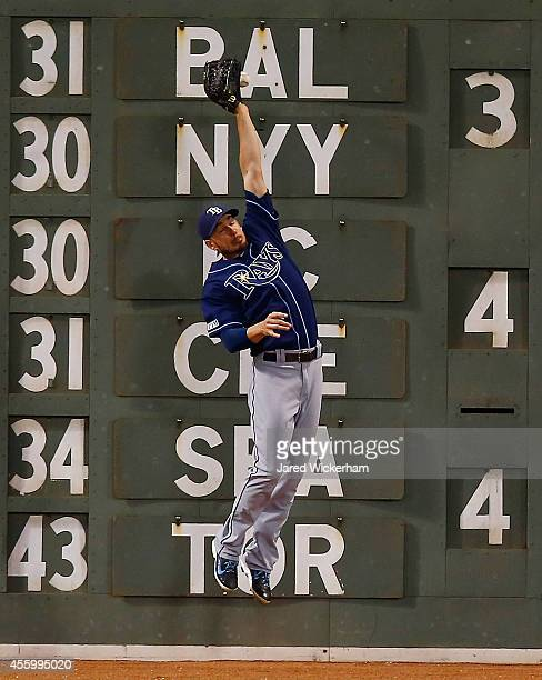 Matt Joyce of the Tampa Bay Rays misplays a fly ball along the wall in left field against the Boston Red Sox in the fourth inning during the game at...