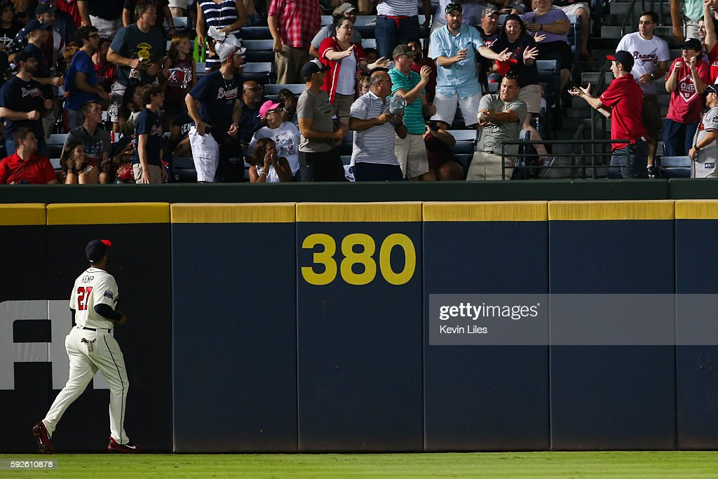 Matt Kemp #27 of the Atlanta Braves watches as a fan tries to catch a three-run home run by Trea Turner #7 of the Washington Nationals in the fourth inning at Turner Field on August 20, 2016 in Atlanta, Georgia.