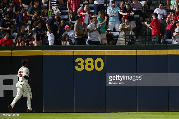 Matt Kemp of the Atlanta Braves watches as a fan tries to catch a threerun home run by Trea Turner of the Washington Nationals in the fourth inning...