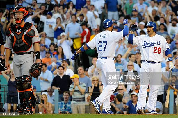 Matt Kemp of the Los Angeles Dodgers celebrates with Rod Barajas after scoring on a throwing error by Buster Posey of the San Francisco Giants in the...
