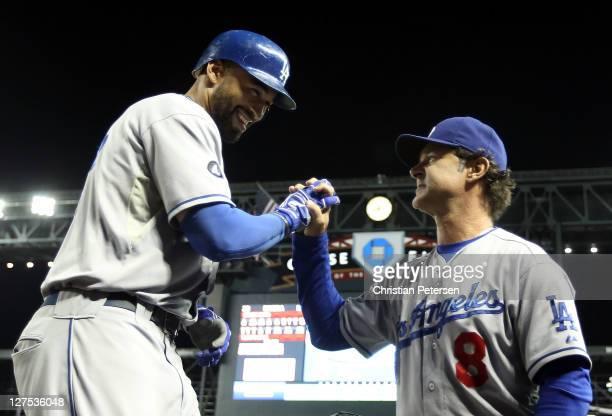 Matt Kemp of the Los Angeles Dodgers highfives manager Don Mattingly after hitting a tworun home run against the Arizona Diamondbacks during the...