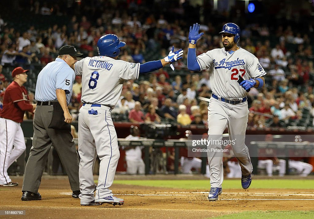 Matt Kemp #27 of the Los Angeles Dodgers high-fives Shane Victorino #8 after both scored first inning runs against the Arizona Diamondbacks during the MLB game at Chase Field on September 12, 2012 in Phoenix, Arizona.