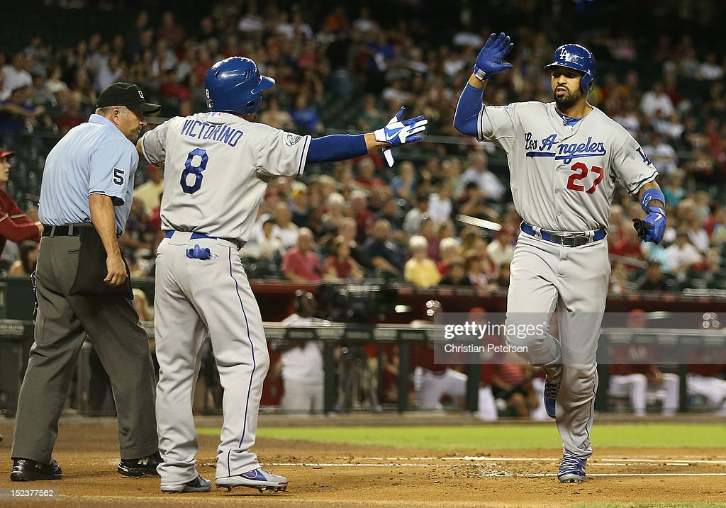 Matt Kemp #27 of the Los Angeles Dodgers high-fives Shane Victorino #8 after both scored first inning runs against the Arizona Diamondbacks during the MLB game at Chase Field on September 12, 2012 in Phoenix, Arizona. The Diamondbacks defeated the Dodgers 3-2.