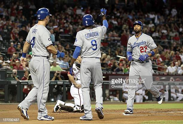 Matt Kemp of the Los Angeles Dodgers is greeted by Jerry Sands and Dee Gordon after Kemp hit a threerun home run against the Arizona Diamondbacks...