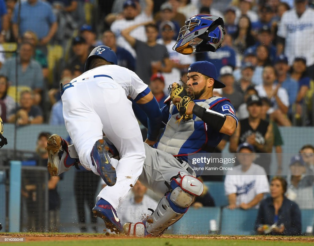 Matt Kemp #27 of the Los Angeles Dodgers is out at the plate as he collides with Robinson Chirinos #61 of the Texas Rangers in the third inning at Dodger Stadium on June 13, 2018 in Los Angeles, California. A benches clearing brawl erupted with Kemp being ejected from the game.