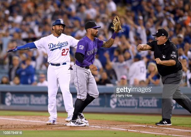 Matt Kemp of the Los Angeles Dodgers reacts with Ian Desmond of the Colorado Rockies as he is called out by umpire Tony Randazzo after his RBI single...