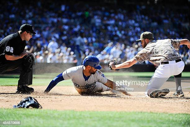 Matt Kemp of the Los Angeles Dodgers scores ahead of the tag of Jesse Hahn of the San Diego Padres during the eighth inning of a baseball game at...