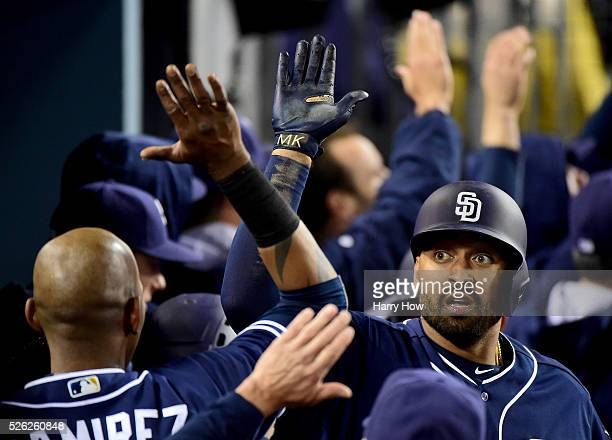 Matt Kemp of the San Diego Padres celebrates his three run homerun with Alexei Ramirez to take a 41 lead over the Los Angeles Dodgers during the...