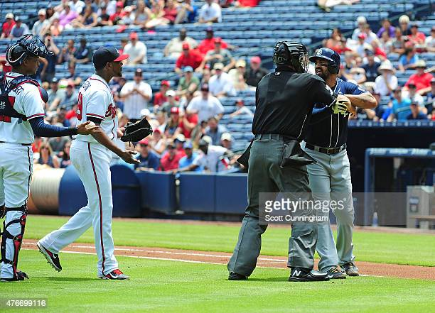 Matt Kemp of the San Diego Padres is restrained by Home Plate Umpire Jordan Baker after being hit by a pitch in the first inning by Julio Teheran of...