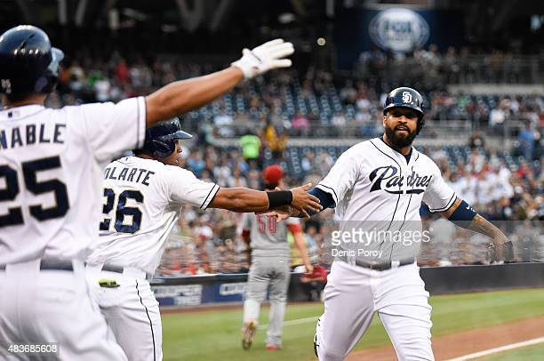 Matt Kemp of the San Diego Padres right is congratulated by Yangervis Solarte and Will Venable after scoring during the first inning of a baseball...