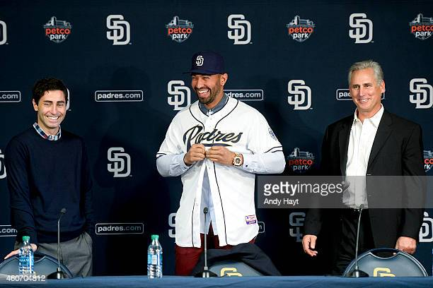 Matt Kemp puts on his uniform top with Manager Bud Black and General Manager AJ Preller of the San Diego Padres at a press conference introducing...