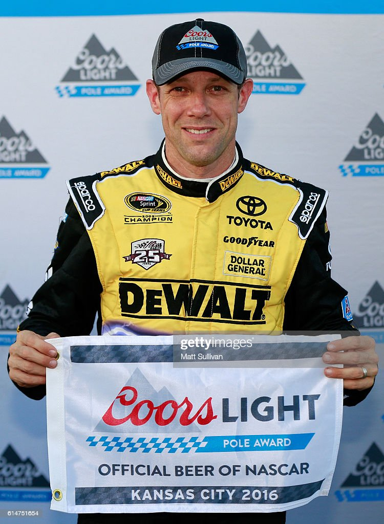Matt Kenseth, driver of the #20 DEWALT FLEXVOLT Toyota, poses with the Coors Light Pole Award after qualifying in the pole position for the NASCAR Sprint Cup Series Hollywood Casino 400 at Kansas Speedway on October 14, 2016 in Kansas City, Kansas.
