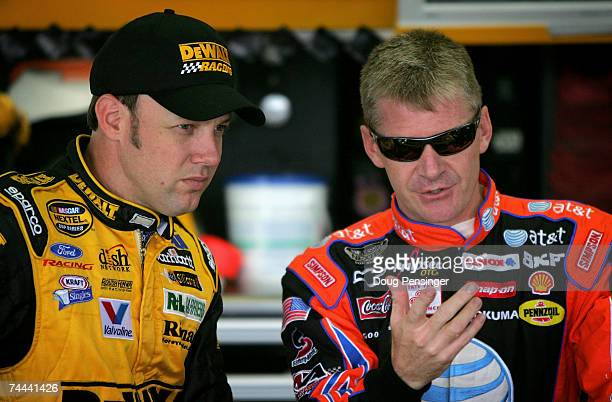 Matt Kenseth driver of the DeWalt Ford talks with Jeff Burton driver of the ATT Mobility Chevrolet in the garage during practice for the NASCAR...