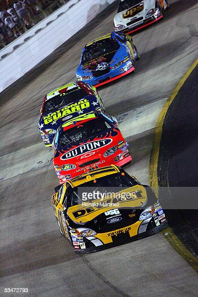 Matt Kenseth driver of the DeWalt Power Tools Ford leads Jeff Gordon driver of the DuPont Chevrolet and Greg Biffle driver of the National Guard Ford...