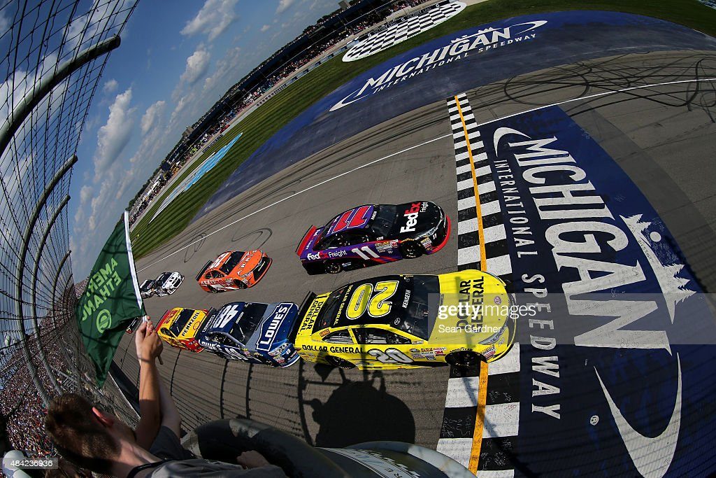 Matt Kenseth, driver of the #20 Dollar General Toyota, and Denny Hamlin, driver of the #11 FedEx Freight Toyota, lead the field at the start of the NASCAR Sprint Cup Series Pure Michigan 400 at Michigan International Speedway on August 16, 2015 in Brooklyn, Michigan.