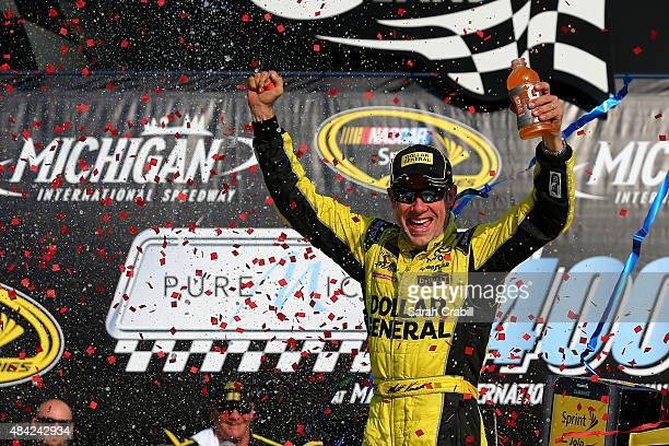 Matt Kenseth driver of the Dollar General Toyota celebrates in victory lane after winning the NASCAR Sprint Cup Series Pure Michigan 400 at Michigan...