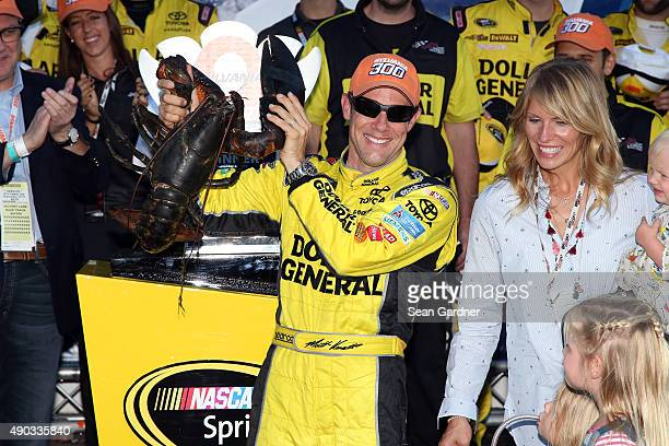 Matt Kenseth driver of the Dollar General Toyota celebrates in Victory Lane with a lobster after winning the NASCAR Sprint Cup Series SYLVANIA 300 at...