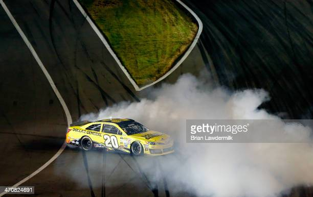 Matt Kenseth driver of the Dollar General Toyota celebrates with a burnout after winning the NASCAR Sprint Cup Series Budweiser Duel 1 at Daytona...