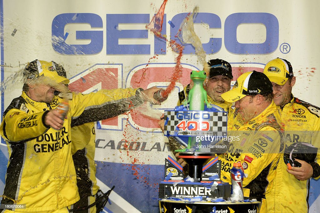 Matt Kenseth, driver of the #20 Dollar General Toyota, celebrates with his crew in victory lane following his win in the NASCAR Sprint Cup Series Geico 400 at Chicagoland Speedway on September 15, 2013 in Joliet, Illinois.