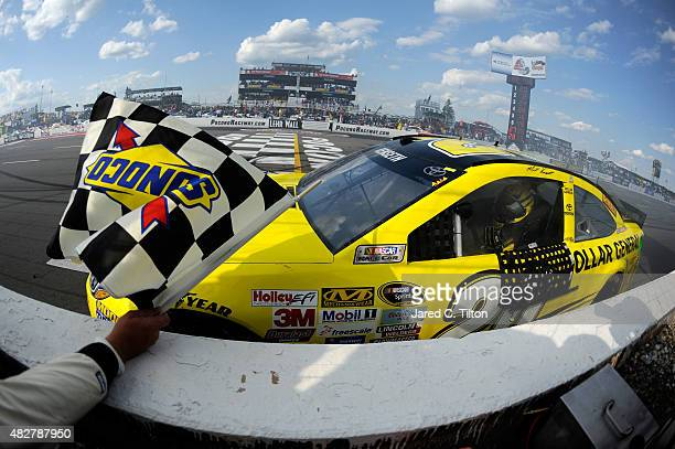 Matt Kenseth driver of the Dollar General Toyota celebrates with the checkered flag after winning the NASCAR Sprint Cup Series Windows 10 400 at...