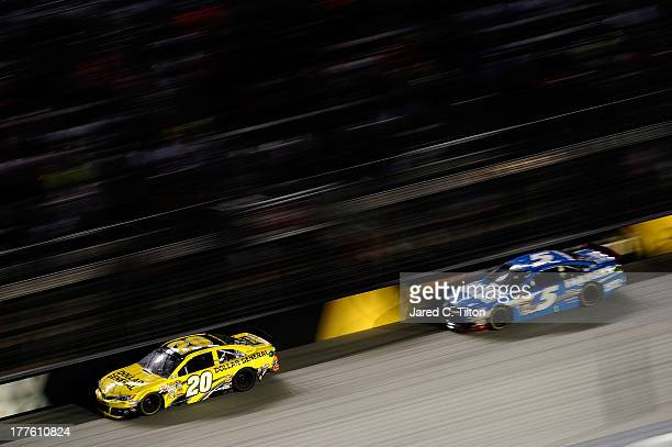 Matt Kenseth driver of the Dollar General Toyota leads Kasey Kahne driver of the Farmers Insurance Chevrolet during the NASCAR Sprint Cup Series 53rd...